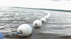 Bouy line floating in rippling water Stock Footage