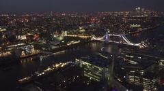Stock Video Footage of ULTRA HD 4K Aerial view London skyline night Tower Bridge traffic Canary Wharf
