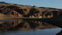 SLOW PAN ACROSS CALM WATER AND LARGE DESERT HILLS EVENING LIGHT Stock Footage