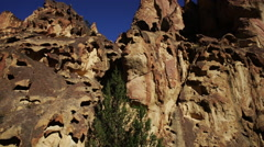PAN ACROSS LARGE ROCK FORMATIONS AND BLUE SKY IN DESERT Stock Footage