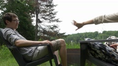 Couple grabs hand while relaxing in chair near fire pit at cottage Stock Footage
