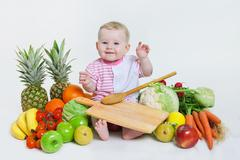 Cute baby sitting with fruits and vegetables Stock Photos