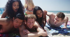 Fun young group of multi ethnic friends running to beach shore Stock Footage