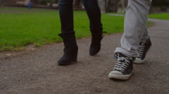 Two pairs of feet walking down a path in the park Stock Footage