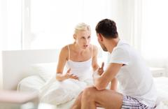unhappy couple having argument at bedroom - stock photo