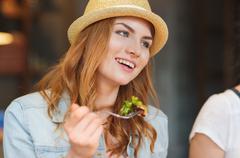 Stock Photo of happy young woman eating salad at bar or pub