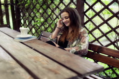 Young girl sitting in the arbour and talking on cellphone Stock Footage