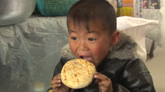 Chinese village boy eating bread - stock footage