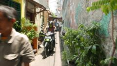 Sunny narrow alley, walk through, man and lady on motorbike ahead - stock footage