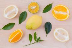 Mixed citruses fruit oranges, lemon on wooden background with orange leaf. - stock photo