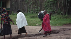 Poor African women carry heavy load with coal in Maralal, Samburu, Kenya Stock Footage