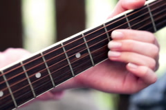 Woman touching strings and playing on the guitar Stock Footage