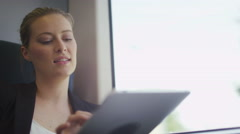 Attractive business woman on a train using her tablet device - stock footage