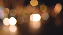 Bokeh of cars driving by and city lights at night Stock Footage