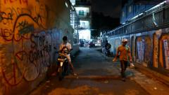 Dark alley, night urban street, boy on motorbike with phone, man walk aside Stock Footage