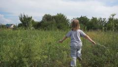 Happy child running through a meadow Stock Footage