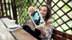 Woman sitting in the arbour and doing selfie on tablet Stock Footage