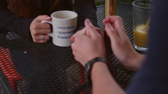 Close-up of a young couple holding hands at an outdoor table Stock Footage