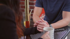A couple having a thumb war at an outdoor table Stock Footage