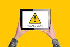 Please Wait Message on Digital Tablet Computer Display - stock photo