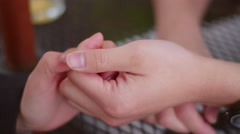Close-up of a young couple holding hands and playing with each other's fingers Stock Footage