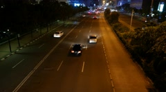 Rare traffic on night street, slide camera high over roadway, perspective view Stock Footage