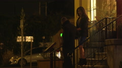 A man lifts his date up off some steps and they walk down the sidewalk Stock Footage