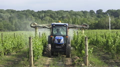 Agricultural farm worker in a tractor spraying pesticides in a vineyard Stock Footage