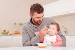 Nice daddy feeding his child - stock photo