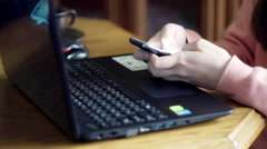 Woman typing message on smartphone at the table Stock Footage