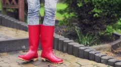 Woman dancing on pavement and wearing red rain boots Stock Footage
