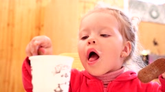 Little girl dunks cookies into a crema of cappuccino and licks it greedily Stock Footage