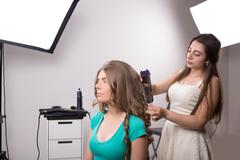 Hairdresser does hair style of woman in hairdressing salon - stock photo