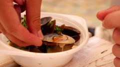 Young attractive bearded man eats mussels with sauce Stock Footage