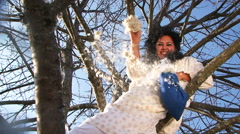 Crazy Dark-Haired Woman In Long White Nightie Throwing Pillow Feathers Sitting Stock Footage