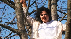 Crazy Dark-Haired Woman In Long White Nightie Sitting On Tree Stock Footage