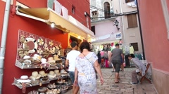 Tourists walking in front of summer hats store Stock Footage