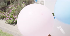 Little Blonde girl running with balloons in slow motion Stock Footage
