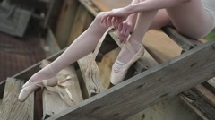Video footage close-up of a ballet dancer tying ribbons on pointe - stock footage