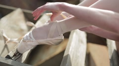 Video footage close-up of a ballet dancer tying ribbons on pointe Stock Footage