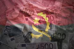 Colorful waving angolan flag on a euro money background Stock Photos