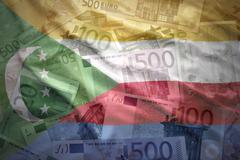 colorful waving comoros flag on a euro money background - stock photo