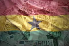 colorful waving ghanaian flag on a euro money background - stock photo