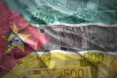 Stock Photo of colorful waving mozambican flag on a euro money background