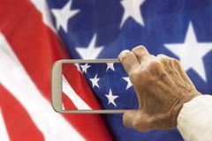 Old hand takes a picture of USA flag, on smart phone. Stock Photos
