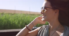 Beautiful Woman enjoying ride in convertible vintage car on road trip with Stock Footage