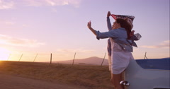 Beautiful Girl friends taking selfies on road trip at sunset with vintage car Stock Footage