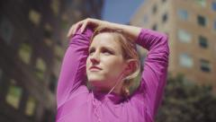 Attractive female stretching before a run in the city in slow motion Stock Footage