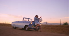 Beautiful Girl friends taking selfies on road trip at sunset with vintage car Arkistovideo