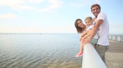 Family standing on a pontoon looking at the sea - stock footage